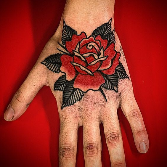 Black and red traditional rose tattoo on the left hand by dennis gutierrez