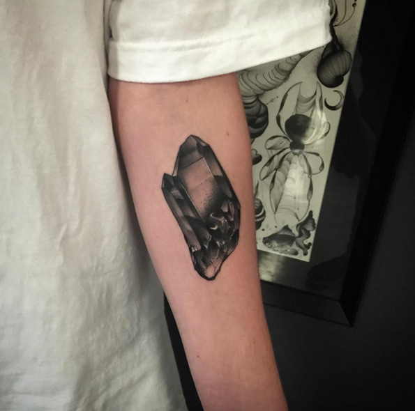 Black crystal tattoo on the left arm