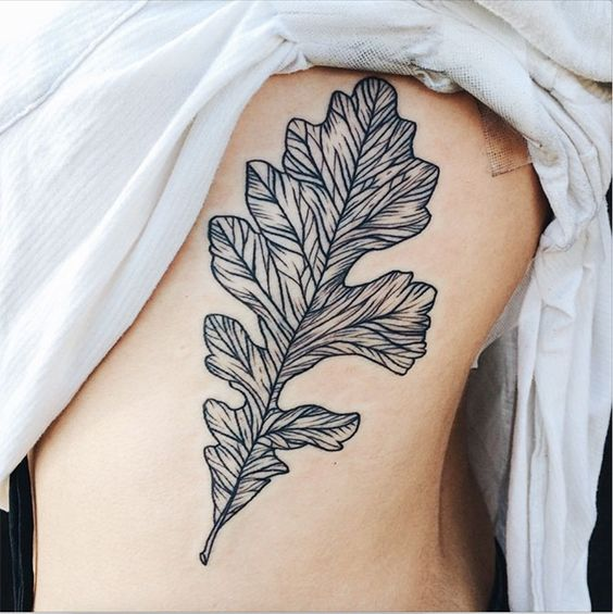 Black detailed oak leaf tattoo on the rib cage