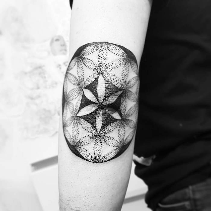 Black dotwork style flower of life tattoo on the elbow by tattooist ninilees