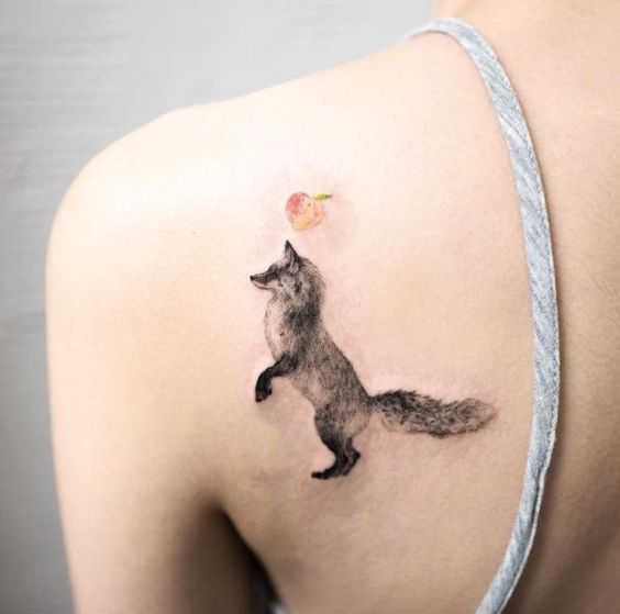 Black fox tattoo with an apple on the left shoulder blade
