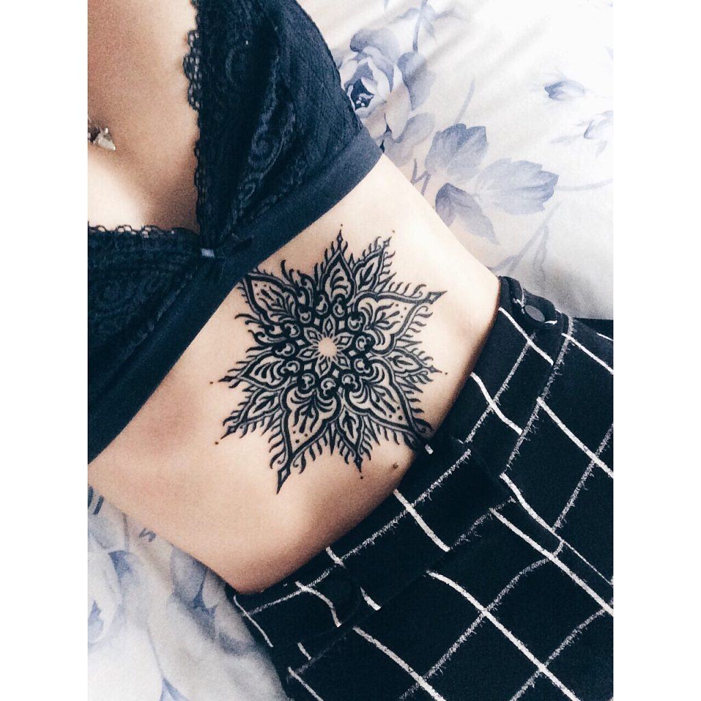 Black mandala sternum tattoo