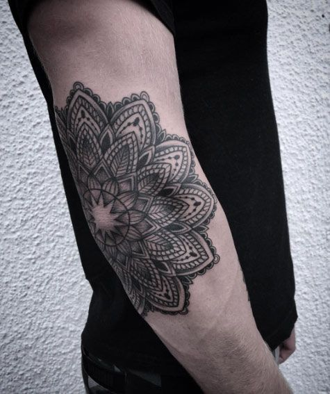 Black mandala tattoo on the right elbow