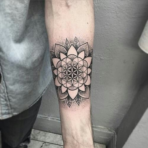 Black negative space mandala tattoo on the left forearm