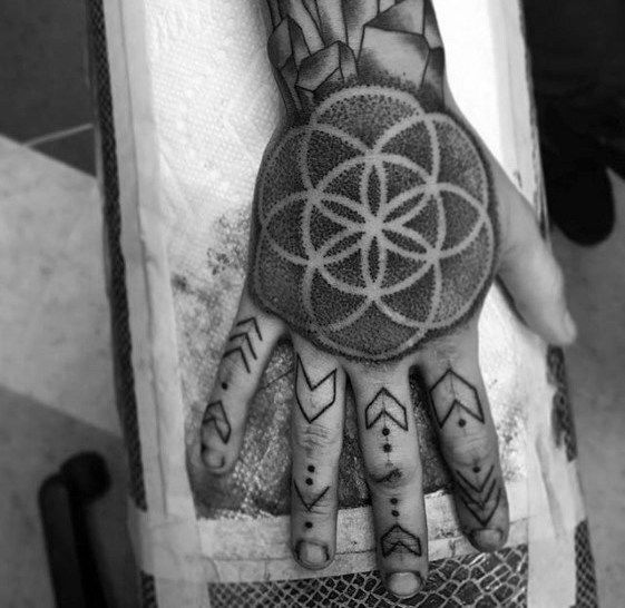 Black negative space sacred geometry tattoo on the hand