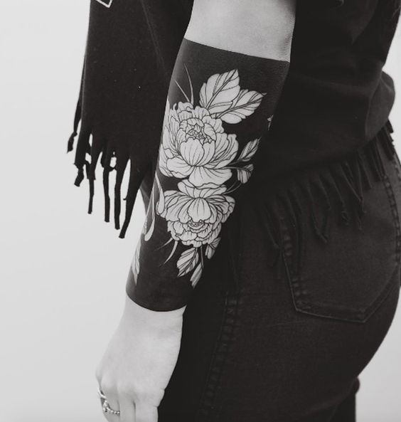 Black out negative space flower tattoo on the left arm