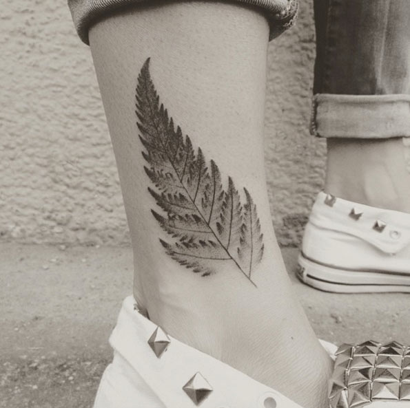 Black small fern tattoo on the ankle by jakub nowicz