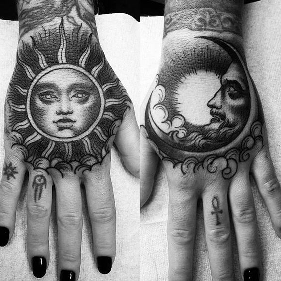 Black sun and moon tattoos on both hands