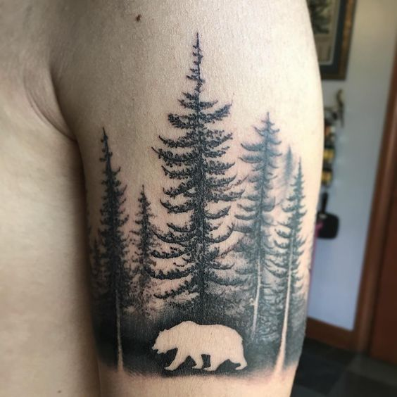 Black tattoo of a negative space bear in the woods