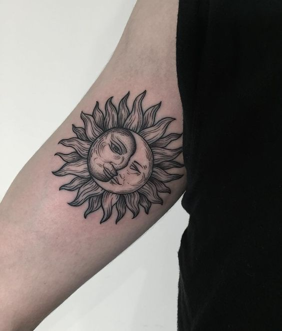 Black traditional sun and moon tattoo on the right arm