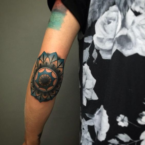 Blue mandala tattoo on the left elbow