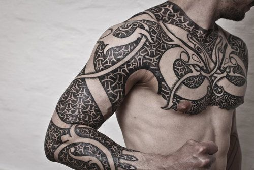 Celtic style negative space chest and arms tattoo