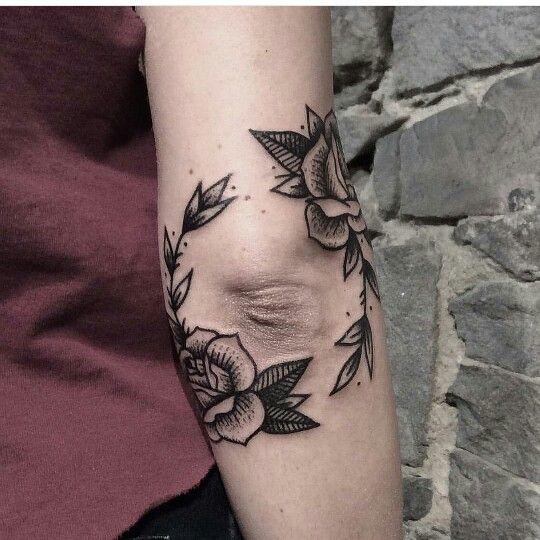 Circular flowers tattoo around the elbow