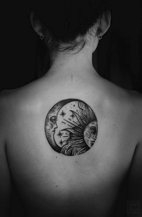 Circular sun and moon black tattoo on the back