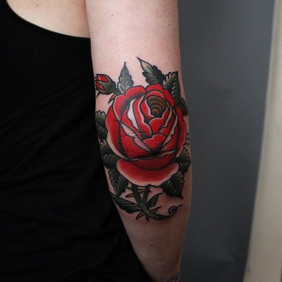 Classic rose tattoo on the right elbow