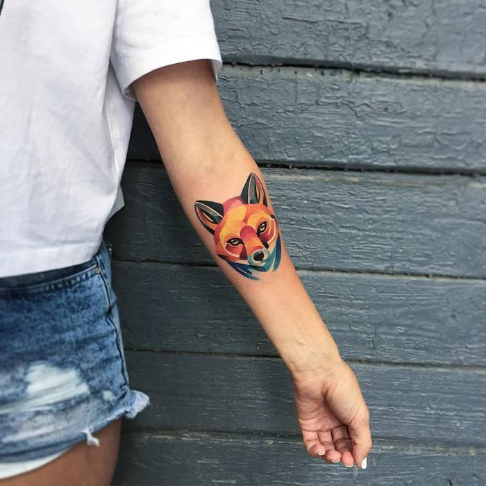 Colorful fox head tattoo on the left inner arm