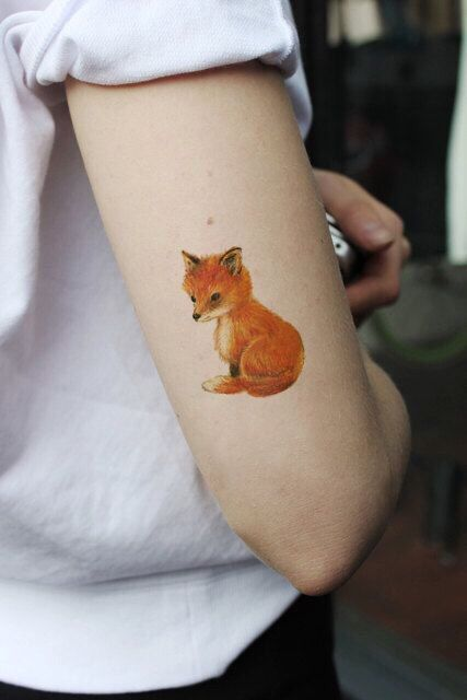 Cute baby fox tattoo on the upper part of the right arm
