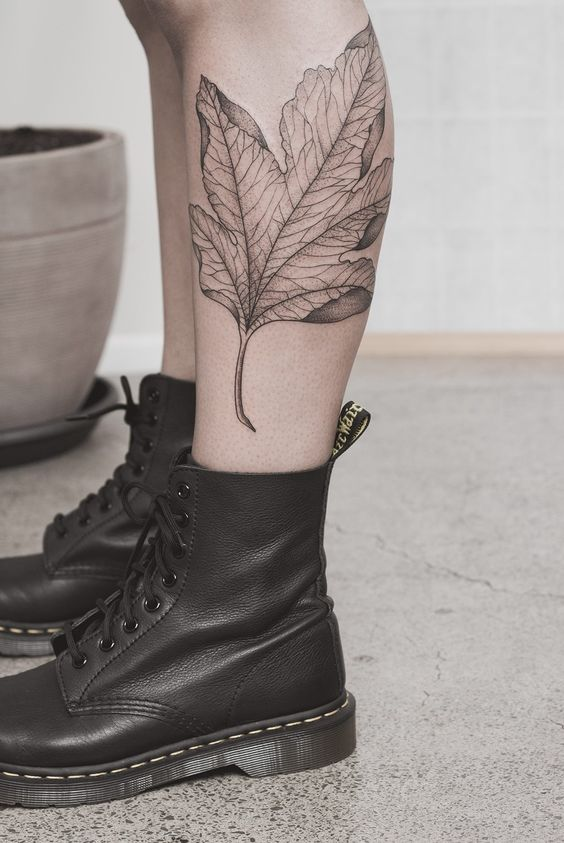 Delicate black maple leaf tattoo on the left calf