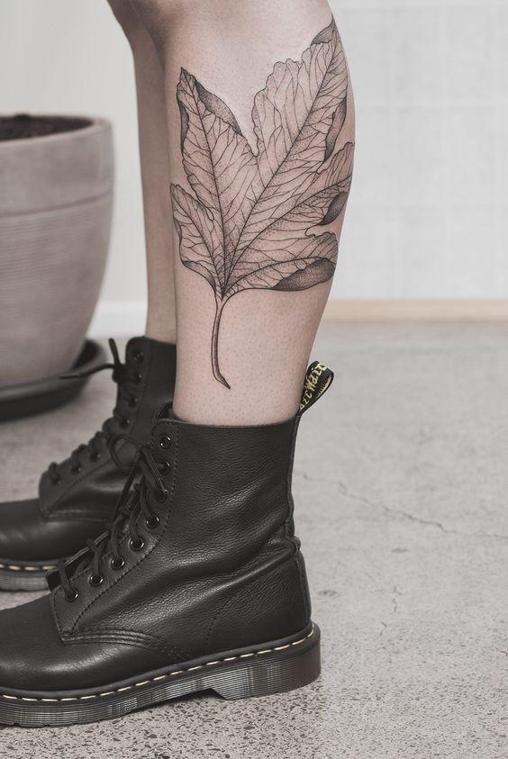 Delicate black maple leaf tattoo on the left calf