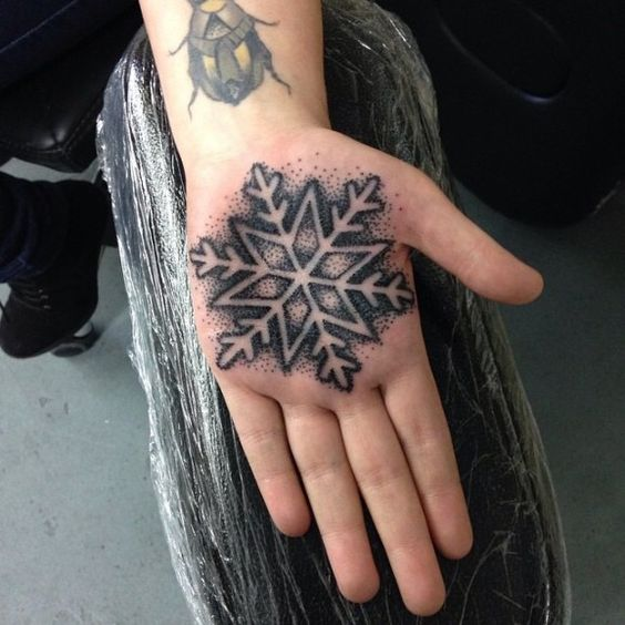Dotwork snowflake tattoo on the left palm