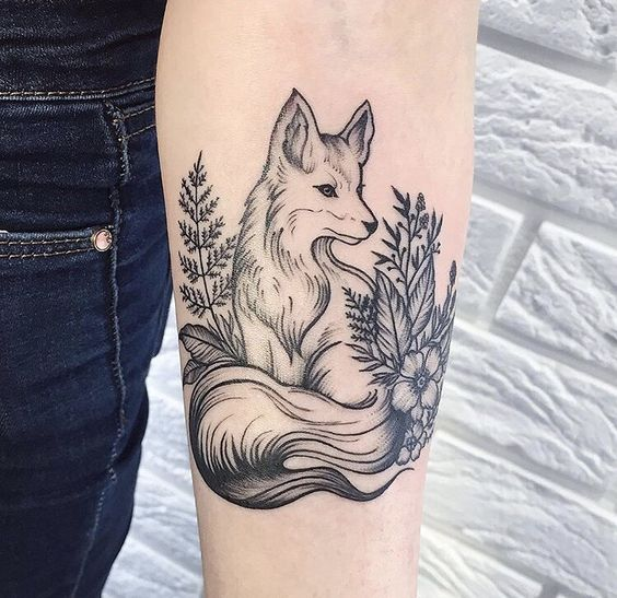 Elegant fox tattoo between the wildflowers and ferns