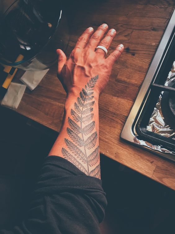 Fern tattoo on the right forearm
