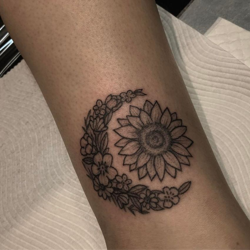 Floral tattoo of a sun and moon on the arm