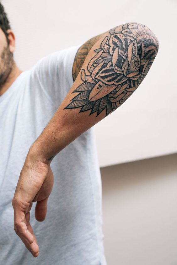 Floral tattoo on the left elbow
