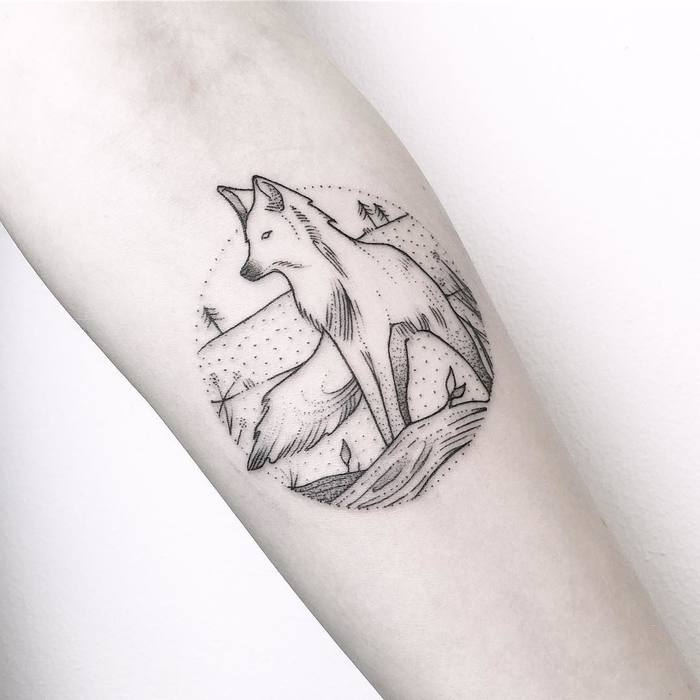 Fox in a nature landscape tattoo on the left inner arm