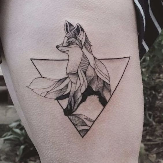 Fox tattoo in a triangle on the left thigh