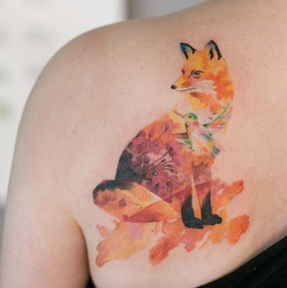 Fox with a hummingbird tattoo on the left shoulder blade