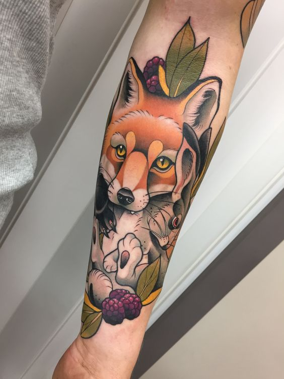 Fox with a rabbit in mouth tattoo on the left arm