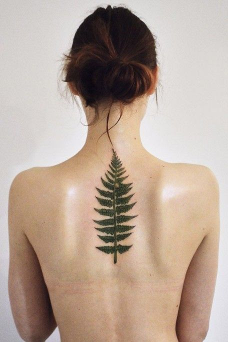 Green fern leaf tattoo on the center of the back by olga nekrasova