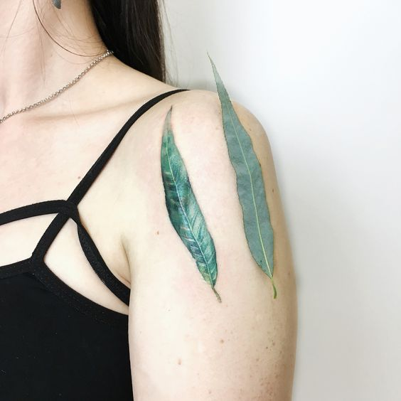 Green willow leaf tattoo on the left shoulder