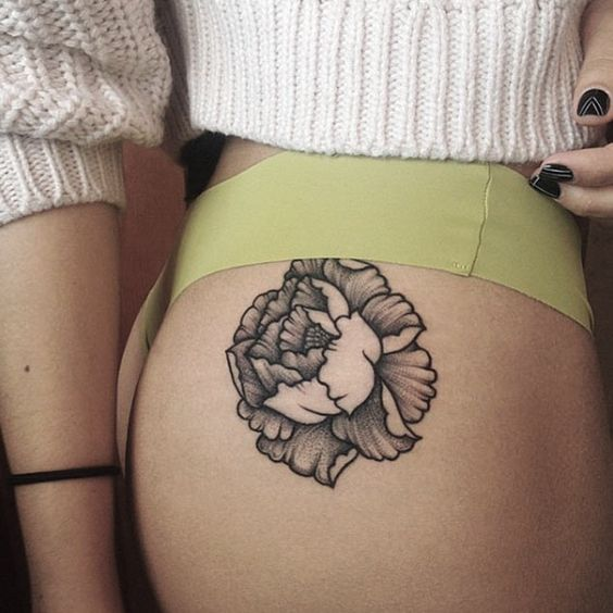 Grey flower tattoo on the right hip by tattooist Sahsa Misiuk