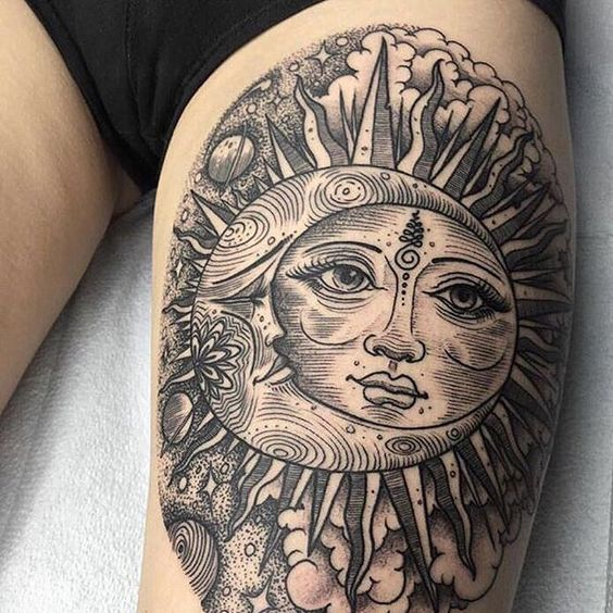 Huge blackwork style tattoo of a sun and moon on the left thigh