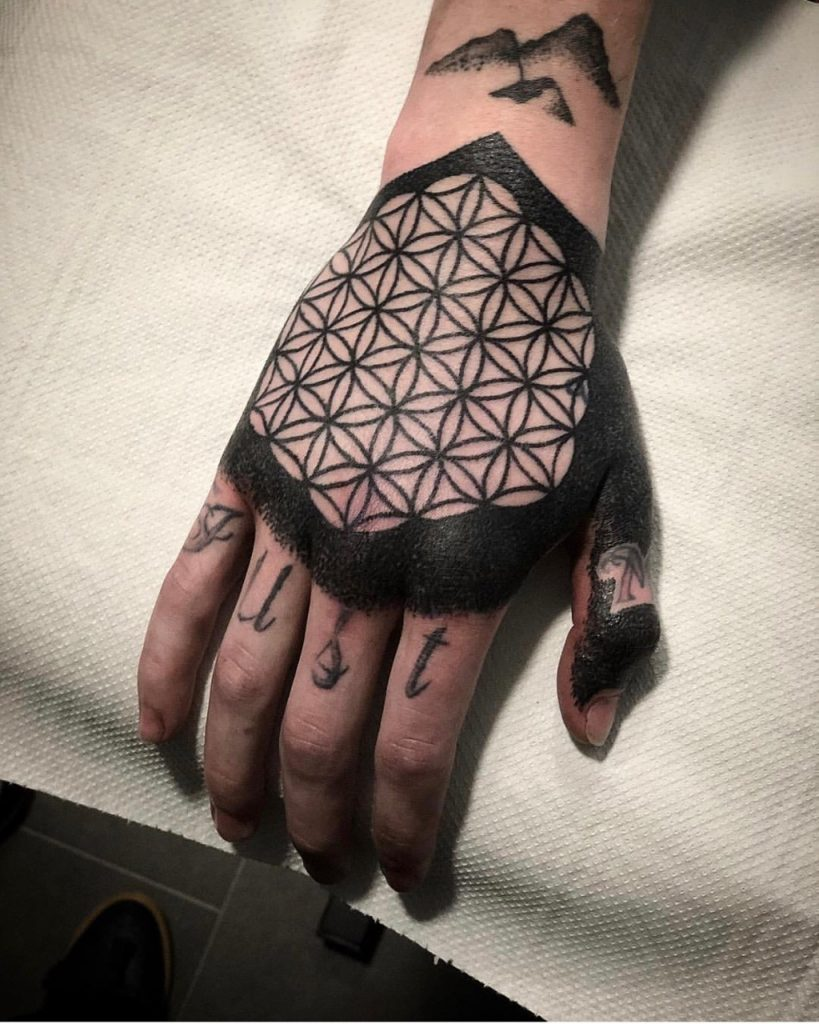 Intense black flower of life tattoo on the right hand