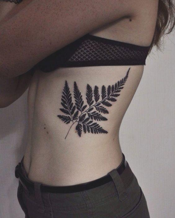 Large black fern leaf tattoo on the left rib cage