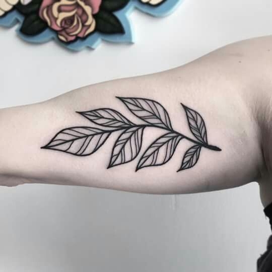 Linear leaves tattoo on the inner arm
