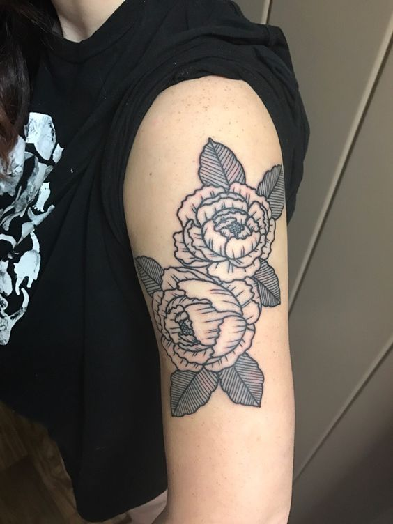 Linear tattoo of a black peony on the arm