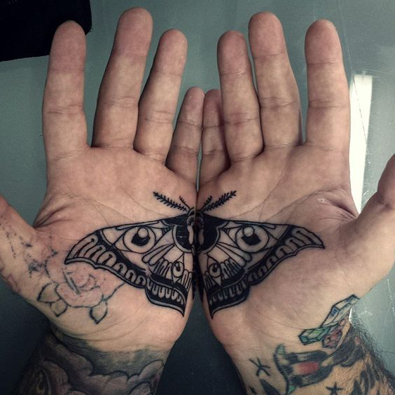 Matching black moth tattoo on both palms