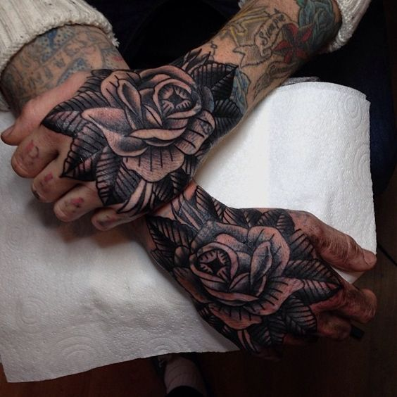 Matching black traditional rose tattoos on both hands by tom flanagan