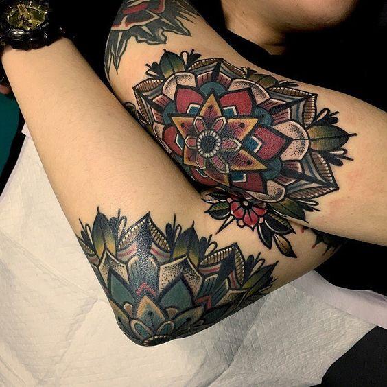 Matching mandala tattoos on both elbows