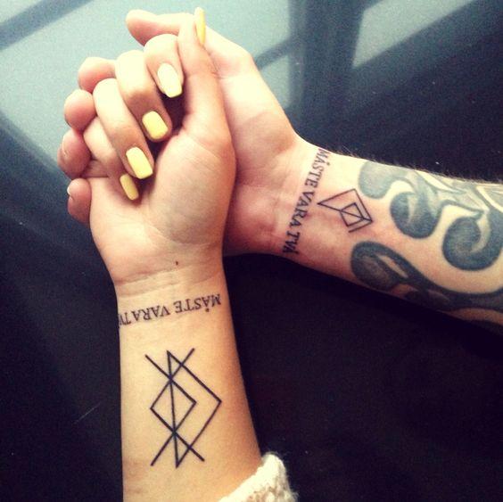 Matching rune tattoos on wrists