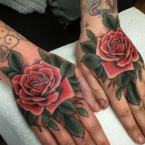 Matching traditional rose tattoos on both hands