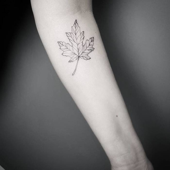 Minimal black maple leaf tattoo on the inner arm