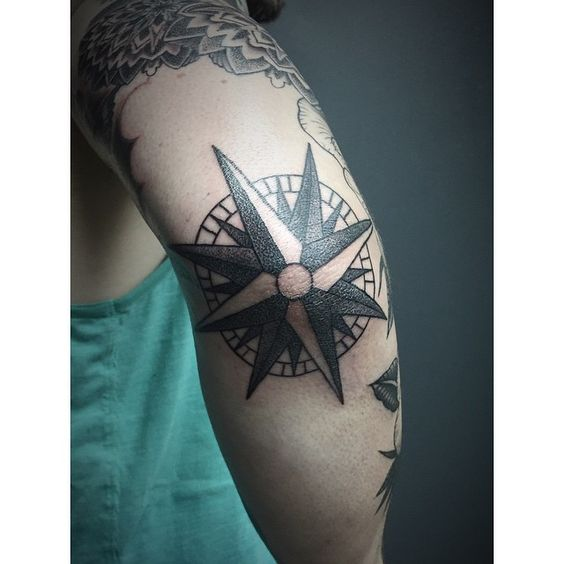 Nautical compass tattoo on the right elbow
