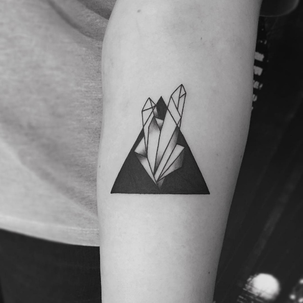 Negative space crystal in a triangle tattoo on the left arm