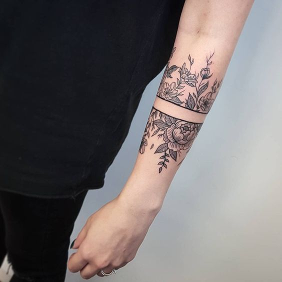 Negative space flower tattoo on the left arm