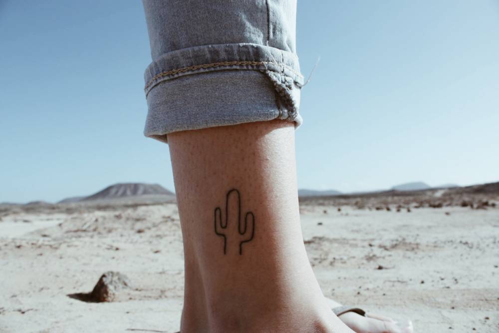 Outline saguaro cactus tattoo on the left inner ankle